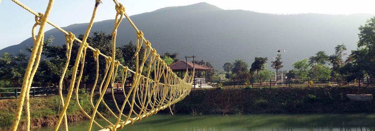 A rope bridge across a large pond situated inside the resort